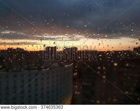 View Of The Sunset In The City Through Glass Wet From Rain