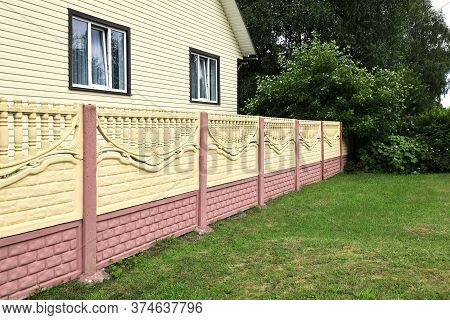 Decorative Concrete Fence Made Of Blocks In A Receding Perspective. Green Plants On The Backdrop On