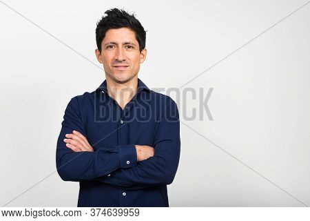 Portrait Of Hispanic Businessman With Arms Crossed