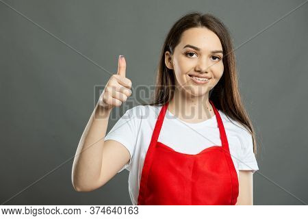 Portrait Of Young Female Supermarket Employee Showing Thumb Up