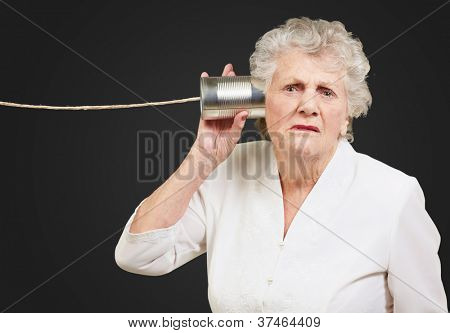 Portrait of a senior woman hearing with metal tin on black background