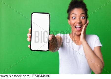 Amazed Black Girl Showing Blank White Smart Phone Screen, Looking At Camera Isolated Over Green Stud