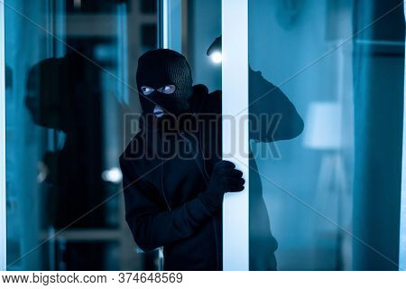 Burglary Concept. Watchful Thief Lurking Into Residential Building Through Open Front Door, Entering