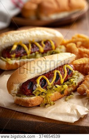 Grilled Hot Dog With Mustard And Relish On A Bun And French Fries On A Rustic Wooden Board