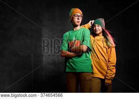 Young Teens Boy And Girl In Green And Yellow Casual Clothing And Hats Standing And Looking At Camera