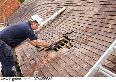 Buckingham, Uk - September 06, 2016. Builder Or Roofing Contractor Removing, Replacing Old Clay Tile
