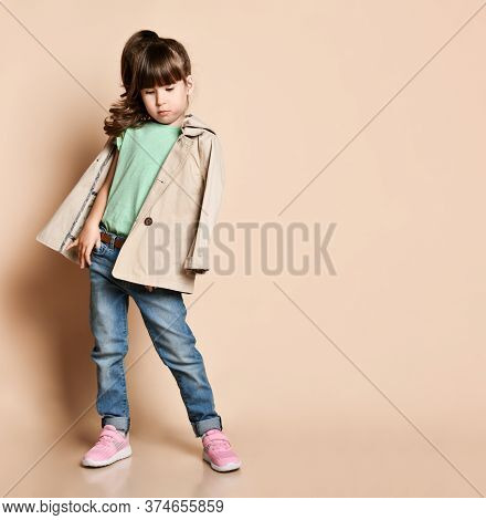Brunette Girl In A Beige Raincoat Holds Her Hand In The Pocket Of Her Jeans. In A Green Blouse, Blue