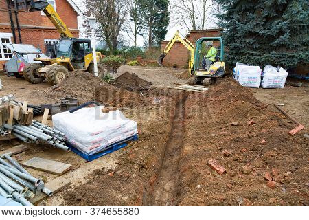 Buckingham, Uk - December 02, 2016. Digger Driver, Digging A Trench For Drains On A Uk Building Site