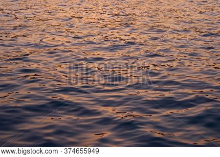 Dark Waters Reflecting The Ochre Colors Of A Sunset Sky.