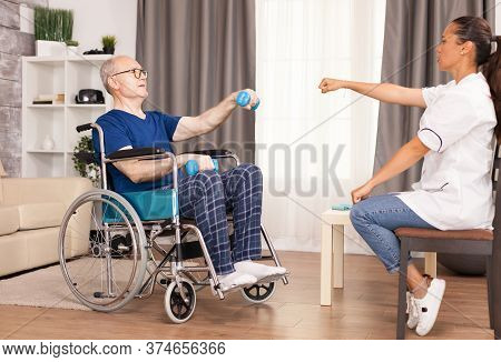 Man In Wheelchair Exercising With Dumbbell For Recovery. Disabled Disability Old Person With Medical