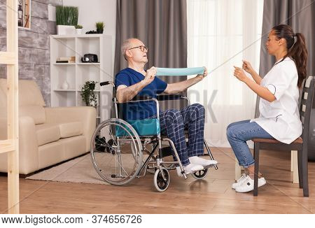 Senior Man With Disability In Wheelchair Doing Recovery Exercise With Resistance Band. Disabled Hand