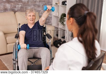 Rehabilitation Treatment For Handicapped Old Woman Sitting On Wheelchair. Disabled Handicapped Old P