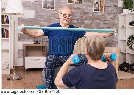 Old Couple Training Their Biceps Using Elastic Band And Weights. Old Person Healthy Lifestyle Exerci