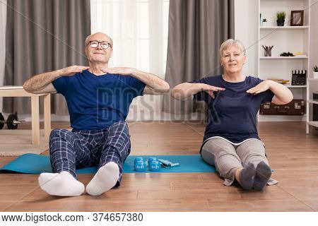 Older People Who Have A Healthy Lifestyle Doing Sport In Living Room. Old Person Healthy Lifestyle E