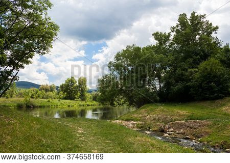 Fresh Green Color Of The Leaves And Grass In The Spring, Surrounding River Vah. Blue Sky With Intens