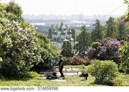 Kyiv, Ukraine - May 10, 2019: View Of Vydubychi Monastery, Dnipro River And Lilac Flowers In Hryshko