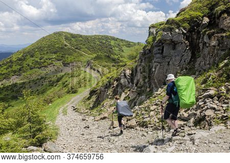 A Pair Of Hikers With Backpacks Descend The Mountain Trail In The Direction Of The Next Peak