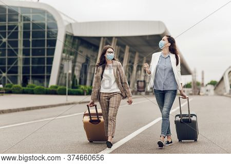 Two Happy Women In Protective Masks After Coronavirus Quarantine With Suitcases Go To The Airport. Y