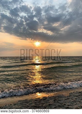 The Setting Sun Is Reflected In The Sea, Leaving A Beautiful Bright Path On The Water.