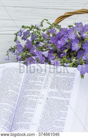 Novomoskovsk, Ukraine - June 15, 2020: Open Bible And Bouquet Flax In Wicker Basket