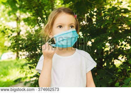Little Cute Girl Take Off Medical Face Mask In The Outdoor, Trees On Background, Close Up. Concept O