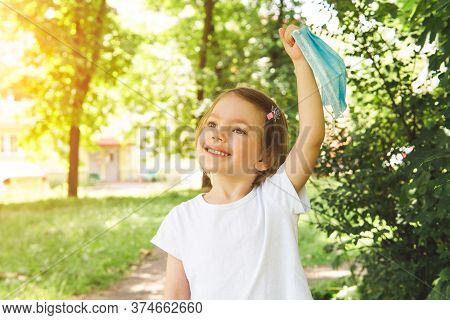 Little Cute Girl Take Off Medical Face Mask With Happy Smile In The Outdoor, Close Up. Concept Of Ha
