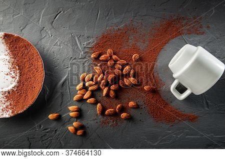 Scattered Cocoa Beans With Shredded Cocoa Beans On A Dark Grey Background With A White Cup And Sauce