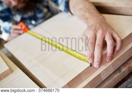 Carpenter as a furniture maker with a tape measure when measuring wood for a shelf