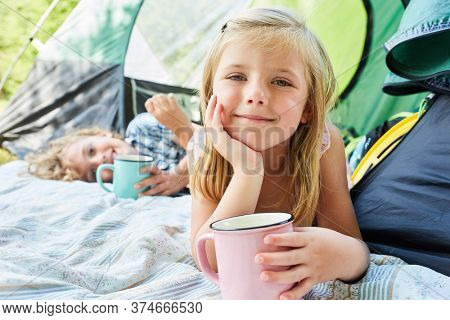 Cute girl with a cup in front of the tent while camping in the summer holidays