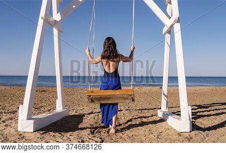 Beautiful Woman Swinging On A Swing At The Fine Sand Enjoying The Idyllic Scene Of The Sun, Sand And