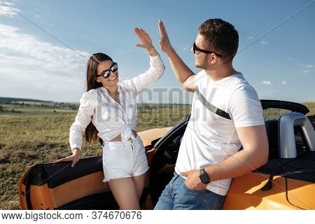 Positive Young Couple Staying In Front Of Convertible Yellow Car. Lovely Couple Giving High Five.