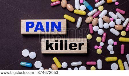 Pain Killer Written On Wood Blocks On A Dark Background Near Multi-colored Pills. Medical Concept