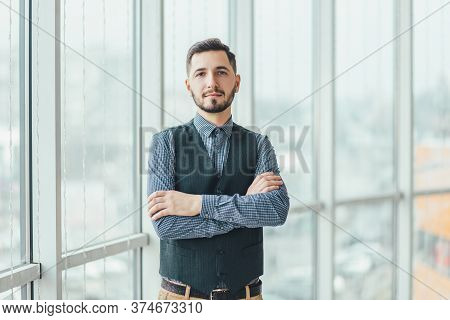 Confident Young Businessman Standing With His Hands Folded, Looking At The Camera, Ready To Hard Wor