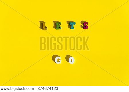 Flat Lay Of Wood Multicolored Letters Is Inscription Of Lets Go With Shadow On Bright Plain Yellow B