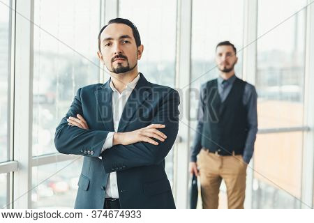 Self-confident Businessman On The Forefront, Looking At The Camera, His Hands Folded, While His Defe