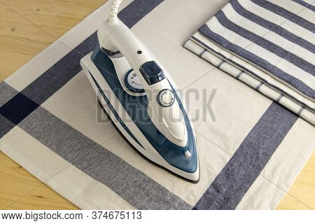 Iron Is An Electrical Appliance For Homework. Ironing Of Textile. Ironing  On The Table.top View.