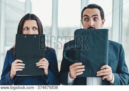 Woman Hiding Her Face Behind Clipboard, Man Hiding His Face Behind Laptop Case.