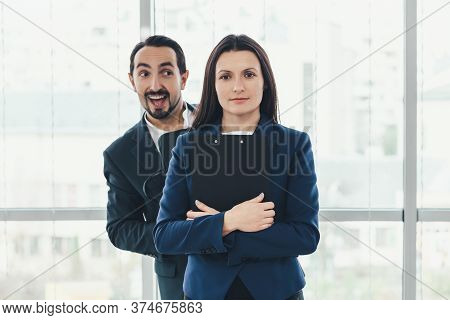 Playful Boss Fussing On His Assistant Back, Flirting Or Making Fun, But Pretty Woman Stands Serious,