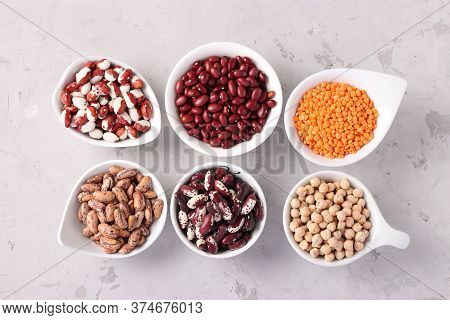Four Varieties Of Beans, Red Lentils And Chickpeas - Protein Rich Beans Are Located On A Gray Concre