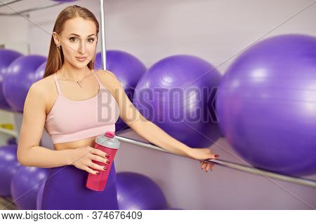 Sporty young girl in sportswear poses with a bottle of water in the fitness center. Wellness. Fitness training.