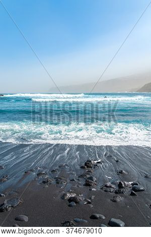 Black Sand Beach With Rocks. Oceanic Waves Crashing. Blue Sky And Mountains In A Fog. Tenerife, Spai