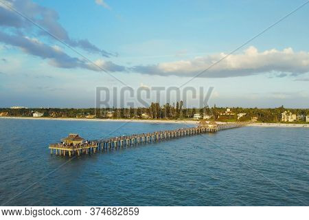 Naples Beach And Fishing Pier At Sunset, Florida. Sunset At The Historic Pier In Naples. Florida, Un