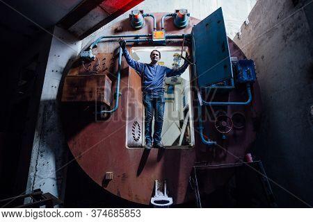 Man In Gateway Corridor Of Airlock Of Abandoned Bunker. Big Hermetic Door Illuminated By Red Lantern