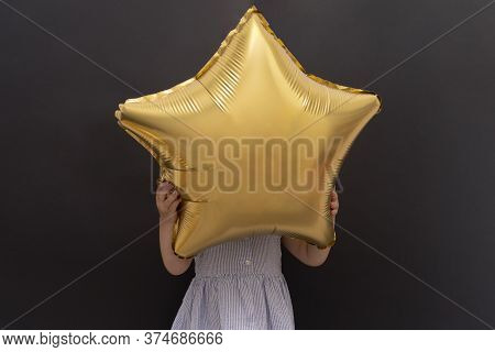 Closeup Of Caucasian Child Hanging Gold Star Balloon With Hands And Hidding Face, Black Background,