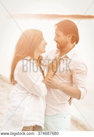 Smiling Couple Stand Embracing By Sea. Side View Of Man And Woman In White Clothes Looking Each Othe