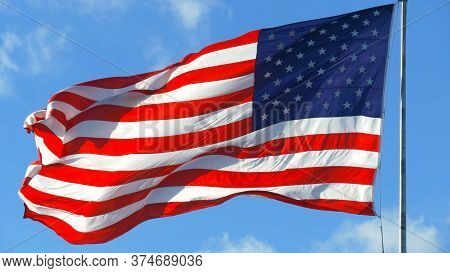 Close Up Of Large American Flag Waving In Front Of Blue Sky And White Cloud. American Flag Waving In