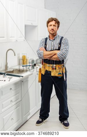 Handsome Plumber With Crossed Arms Looking At Camera Near Tools On Worktop In Kitchen
