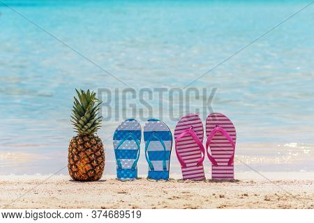 Summer Background With Pineapple And Slippers On A Tropical Beach. Holiday Vacation And Travel Conce