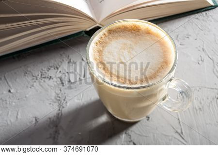 Transparent Cup Of Coffee With Latte Art On Concrete Table With Book