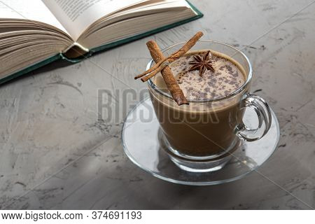 Coffee With Cinnamon And Anise In Transparent Cup And Book On Concrete Table